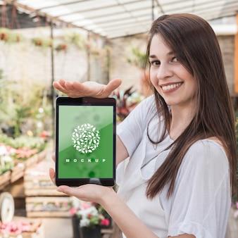 Chica sujetando mockup de tableta con concepto de jardinería