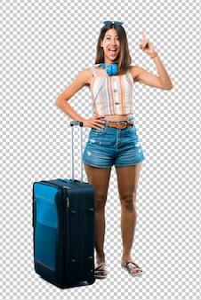 Chica viajando con su maleta de pie y pensando en una idea apuntando el dedo hacia arriba