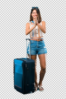 Chica viajando con su maleta sonriendo y aplaudiendo.