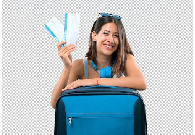 Chica viajando con su maleta sosteniendo boletos de avión