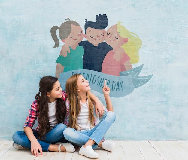 Chicas frente a una pared con una maqueta de dibujos animados