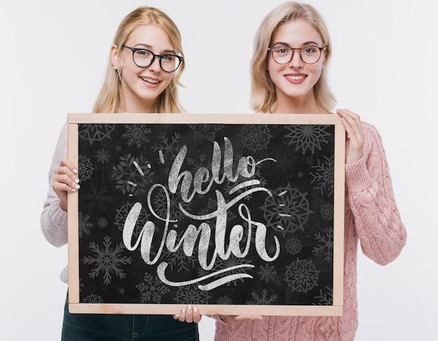 Chicas jóvenes sonrientes con cartel de maqueta
