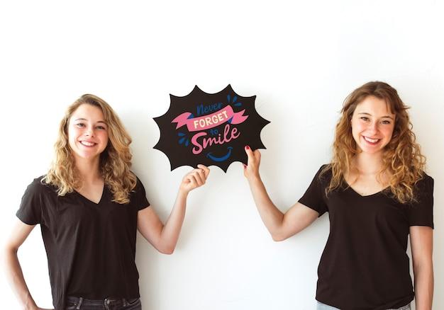 Chicas jóvenes sujetando mockup de burbuja de texto de pizarra