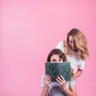 Chicas jóvenes sujetando mockup de cover de libro