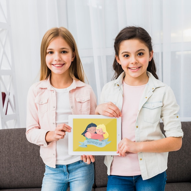 Chicas de pie y sosteniendo una tableta maqueta.