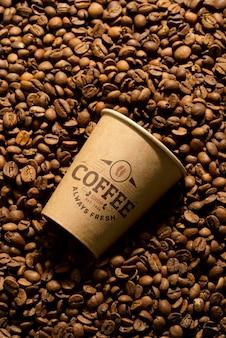Chicchi di caffè aromatici e tazza di carta mockup.