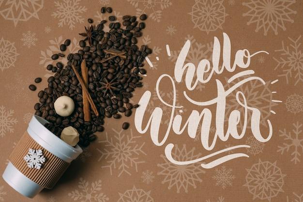 Chicchi di caffè in una tazza con ciao saluto invernale
