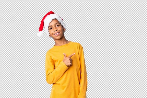Chico afroamericano con sombrero de navidad apuntando hacia un lado para presentar un producto
