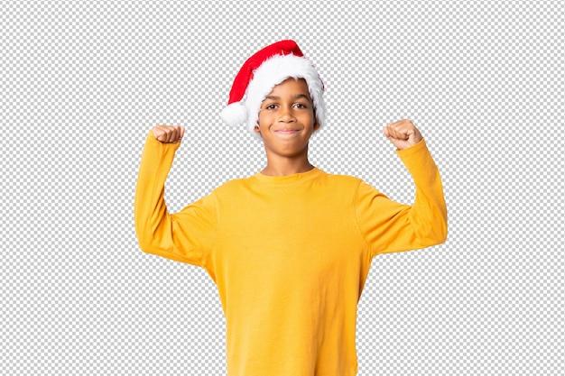 Chico afroamericano con sombrero de navidad celebrando una victoria
