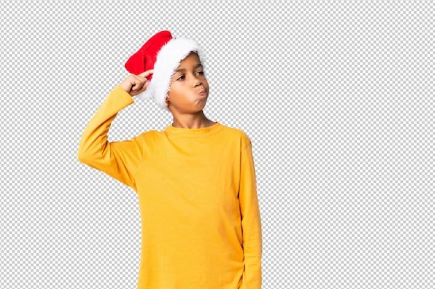 Chico afroamericano con sombrero de navidad con dudas y con expresión de la cara confusa