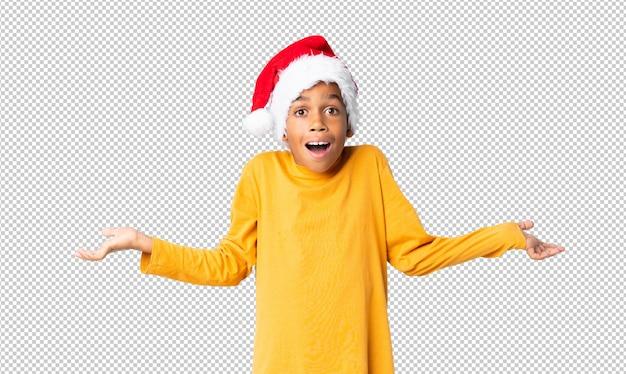 Chico afroamericano con sombrero de navidad con expresión facial sorprendida