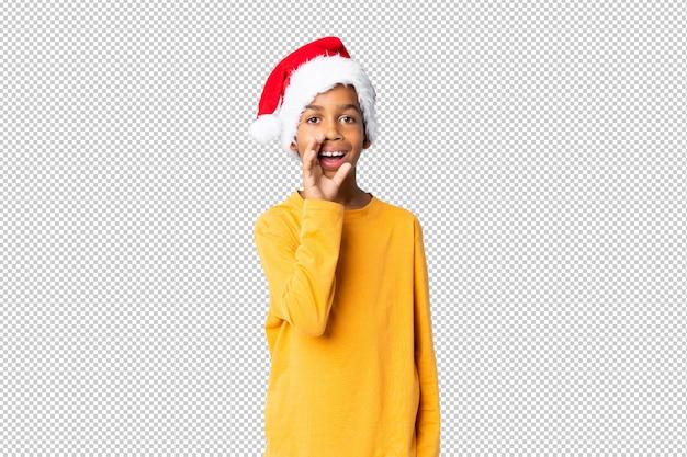 Chico afroamericano con sombrero de navidad gritando con la boca abierta