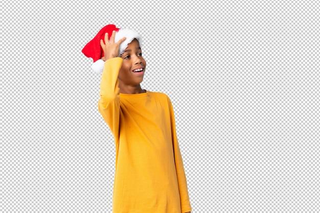 Chico afroamericano con sombrero de navidad se ha dado cuenta de algo y tiene la intención de encontrar la solución