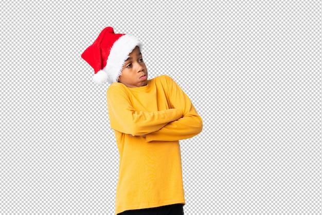 Chico afroamericano con sombrero de navidad haciendo dudas gesto mientras levanta los hombros