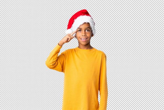 Chico afroamericano con sombrero de navidad con la intención de darse cuenta de la solución