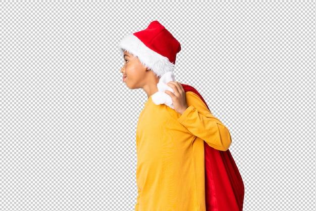 Chico afroamericano con sombrero de navidad y llevar una bolsa con regalos