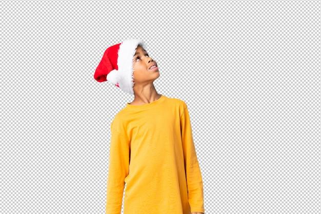 Chico afroamericano con sombrero de navidad mirando hacia arriba mientras sonríe