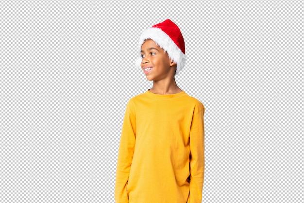 Chico afroamericano con sombrero de navidad mirando hacia el lado