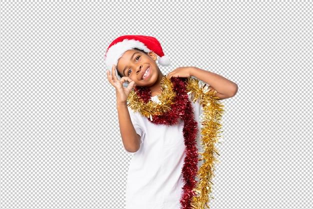 Chico afroamericano con sombrero de navidad mostrando signo ok con los dedos