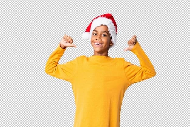 Chico afroamericano con sombrero de navidad orgulloso y satisfecho de sí mismo