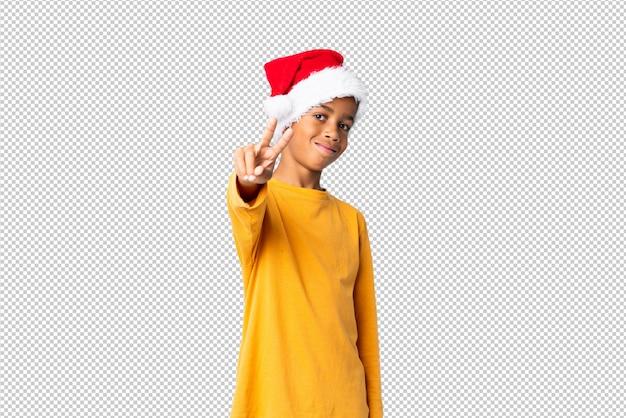 Chico afroamericano con sombrero de navidad sonriendo y mostrando el signo de la victoria