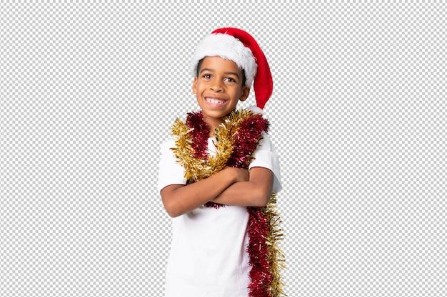 Chico afroamericano con sombrero de navidad sonriendo mucho