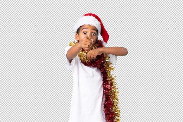 Chico afroamericano con sombrero de navidad sorprendido y apuntando al frente