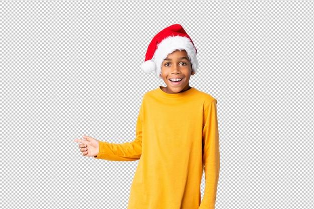 Chico afroamericano con sombrero de navidad sorprendido y apuntando con el dedo al lado