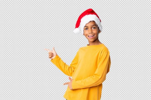 Chico afroamericano con sombrero de navidad sorprendido y apuntando hacia el lado