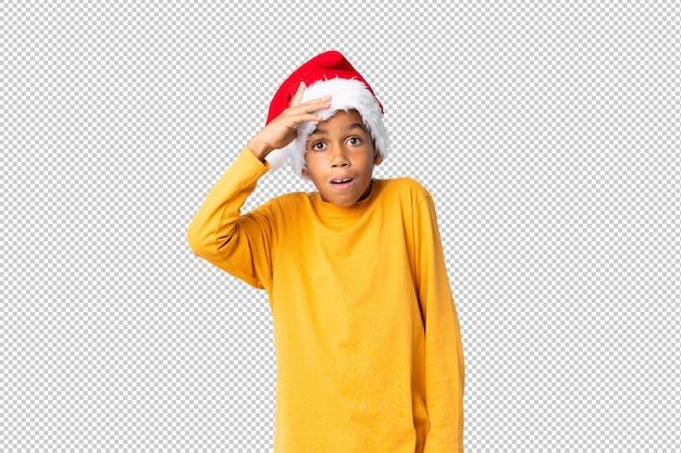 Chico afroamericano con sombrero de navidad con sorpresa y expresión facial sorprendida
