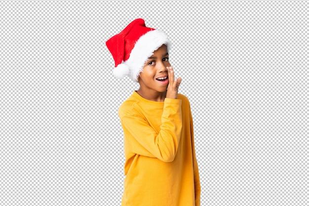 Chico afroamericano con sombrero de navidad susurrando algo