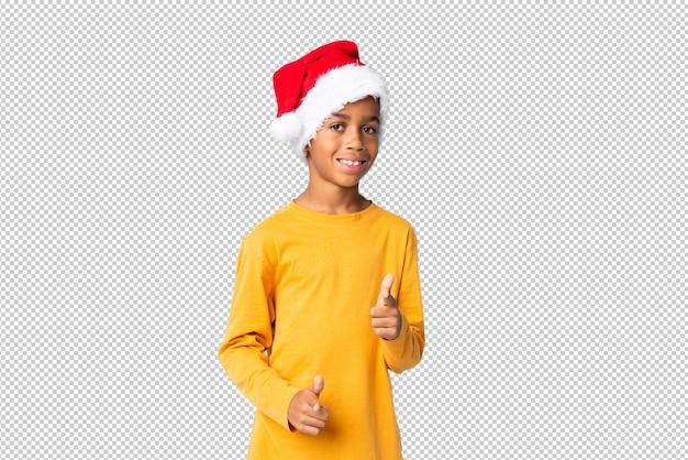 Chico afroamericano con sombrero de navidad te señala con una expresión segura