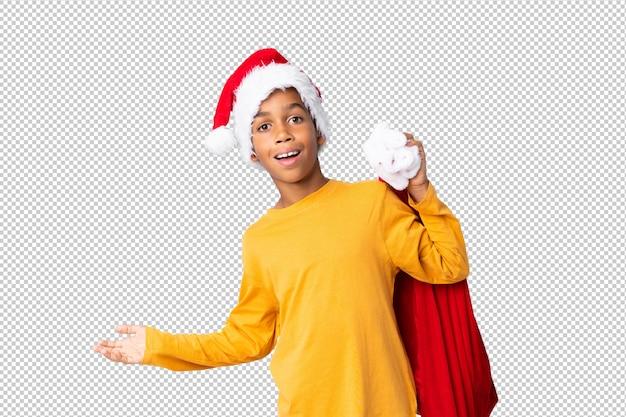 Chico afroamericano con sombrero de navidad y tomando una bolsa con regalos y haciendo gesto de sorpresa