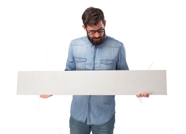 Chico concentrado sujetando un letrero vacío