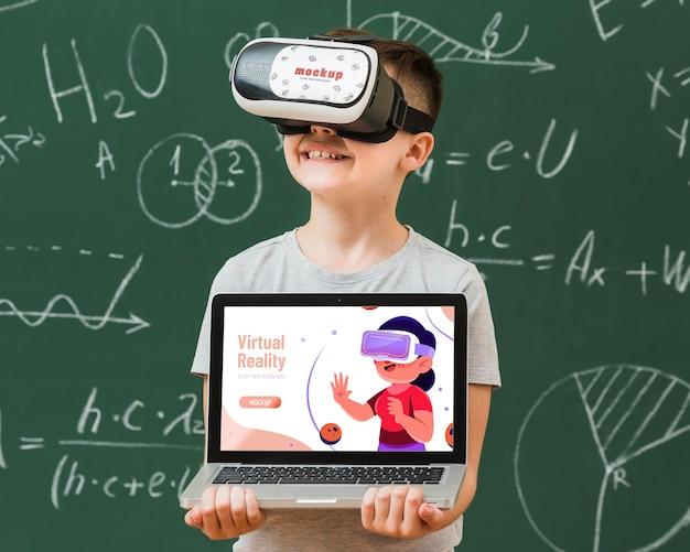 Chico con maqueta de casco de realidad virtual