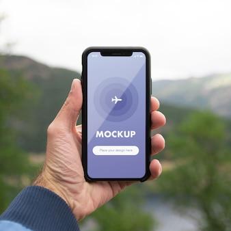 Chiuda sul modello di una mano che tiene il telefono cellulare sullo sfondo delle montagne