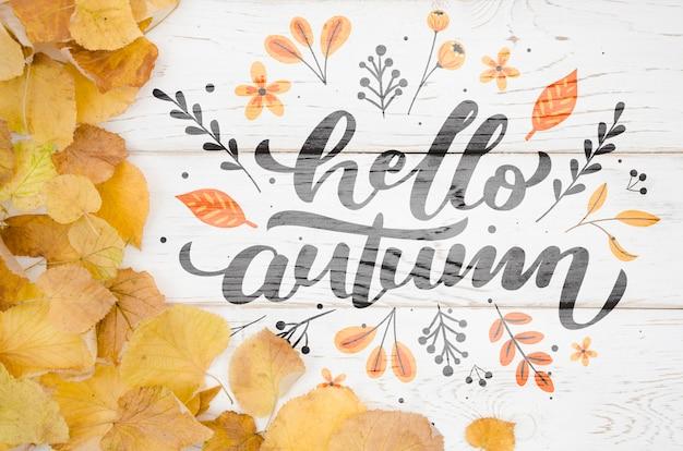 Ciao citazione d'autunno circondata da foglie gialle in un angolo