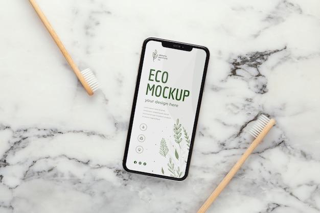 Cierre en maqueta de teléfono inteligente cerca de objetos sostenibles