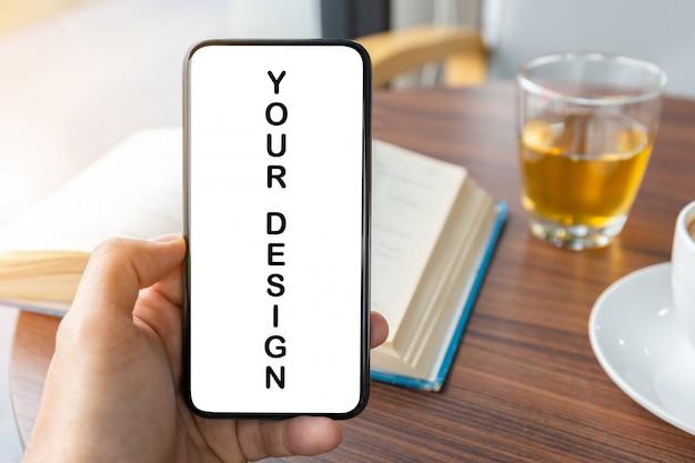 Ciérrese para arriba de la mano del hombre joven usando smartphone móvil con el fondo borroso de la taza de la taza del café con leche y del libro, maqueta.