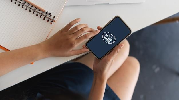 Close-up beeld van vrouw hand met mock up smartphone in werkruimte