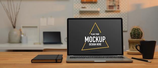 Close-up beeld van werktafel met mockup laptop, koffiekopje en schemaboek