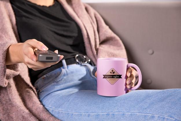Close-up donna con telecomando e tazza