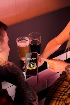 Close-up persone con smartphone e birra