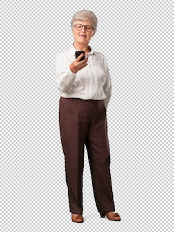 Close-up van de volledig lichaams hogere vrouw van hand wat betreft mobiel, gebruikend internet en sociale networ