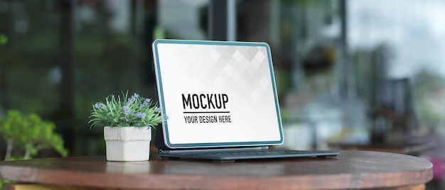 Close-up van draagbare werkruimte met laptop en plant pot op houten tafel