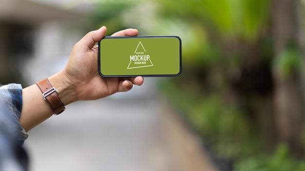 Close-up van een man hand met smartphone mockup