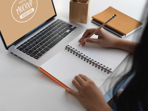 Close-up van kantoormedewerker schrijven op laptop tijdens het gebruik van schermlaptop mockup