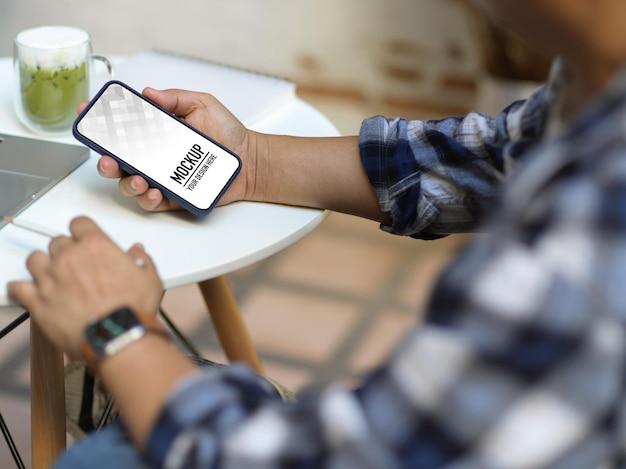 Close up van mannelijke handen met behulp van smartphone zittend in de kantoorruimte