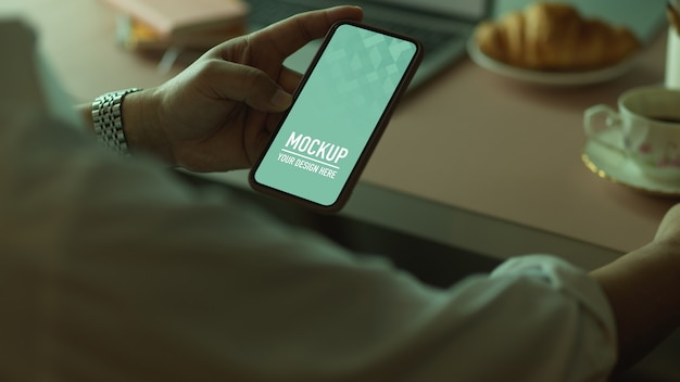 Close-up van mannenhand met smartphone zittend op de werkplek