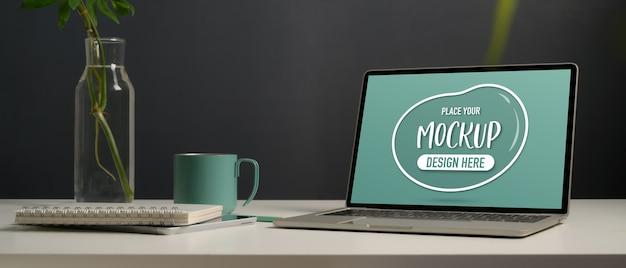 Close-up van mock up laptop, briefpapier, vaas plant en mok op wit bureau in kantoor aan huis